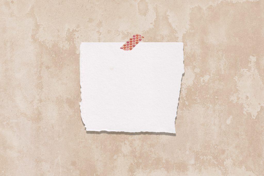 Ein ausgerissenes Stück Papier hängt mit einem Klebestreifen an der Wand