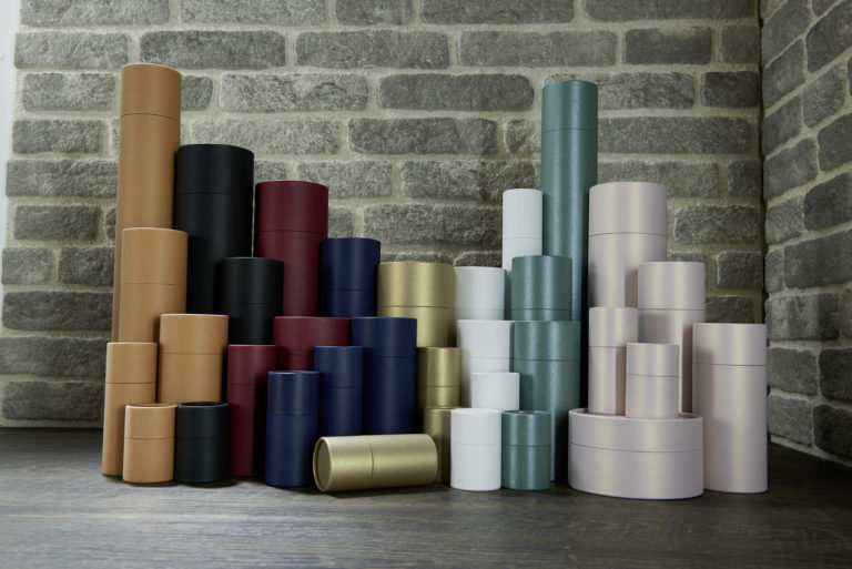 betubed Pappdosensortiment in verschiedenen Farben und Größen, vor einer grauen Steinwand