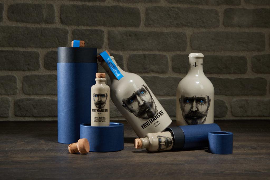 Knut Hansen Gin Flaschen mit zwei dunkelblauen 3-teiligen betubed Pappdosen, vor einer grauen Steinwand
