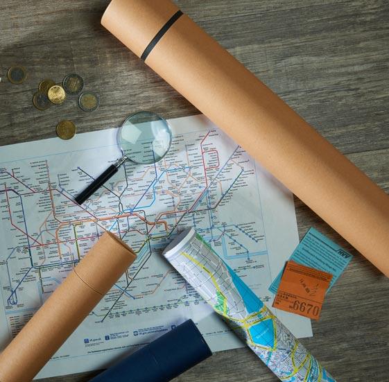 betubed Pappdose mit Landkarten, einer Lupe und Geld