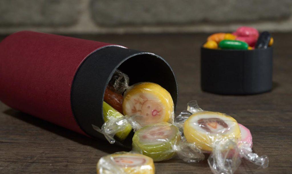 Bordeauxrote runde Pappdose liegend auf Tisch mit Bonbons gefüllt