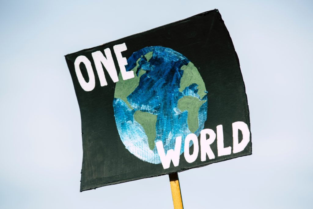 """Schwarzes Demo-Plakat mit einer Weltkugel und der Aufschrift """"One World""""."""